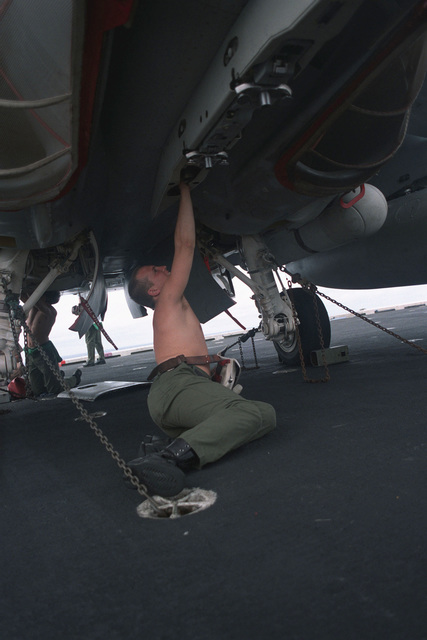 AIRMAN Hayton works on a bomb rack of an F/A-18 Hornet aircraft from Strike-Fighter Squadron 113 (VFA-113) aboard the aircraft carrier USS CONSTELLATION (CV 64)