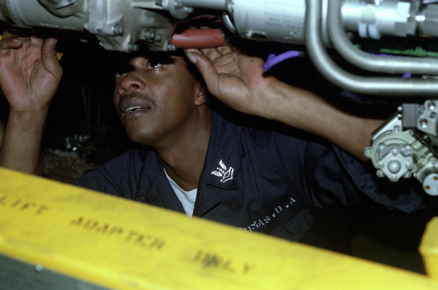 Aviation Machinist Mate Second Classs Thomas, removes a fuel flow transmitter from a jet engine aboard the aircraft carrier USS CONSTELLATION (CV-64)