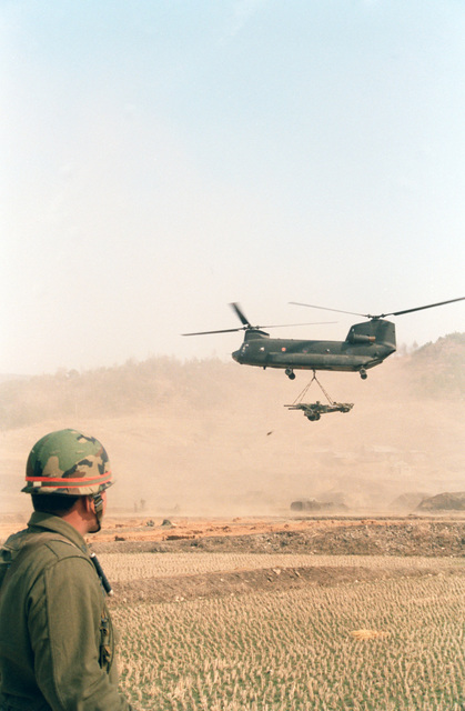 Lieutenant Colonel (LTC) Edward T. Teixeira, Commander,  7th Battalion, 8th Field Artillery Regiment, watches as a CH-47 Chinook helicopter airlifts a pair of howitzers into the battle zone during the joint U.S./South Korean Exercise TEAM SPIRIT'85