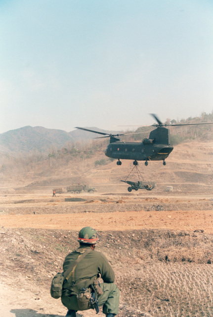 Lieutenant Colonel (LTC) Edward T. Teixeira, Commander,  7th Battalion, 8th Field Artillery Regiment, watches as a CH-47 Chinook helicopter airlifts a howitzer into the battle zone during the joint U.S./South Korean Exercise TEAM SPIRIT'85