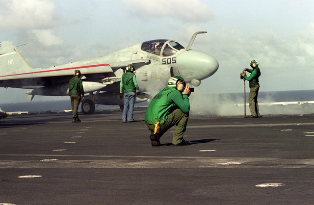 A crewmember takes photographs while an A-6E Intruder aircraft prepares to catapult from the deckof the aircraft carrier USS CONSTELLATION (CV-64)