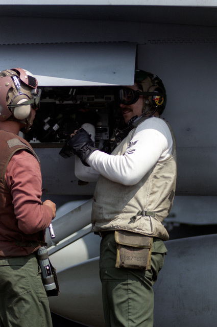 Strike-fighter Squadron 25 (VFA-25) personnel perform a pre-flight safety check on an F/A-18 Hornet aircraft aboard the aircraft carrier USS CONSTELLATION (CV-64)