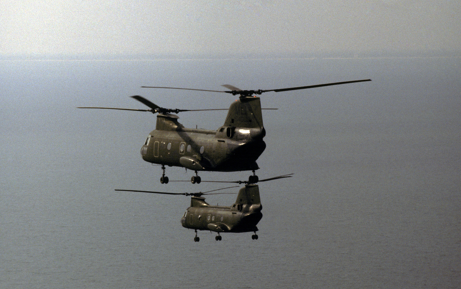 An air-to-air left side view of two CH-46 Sea Knight helicopters