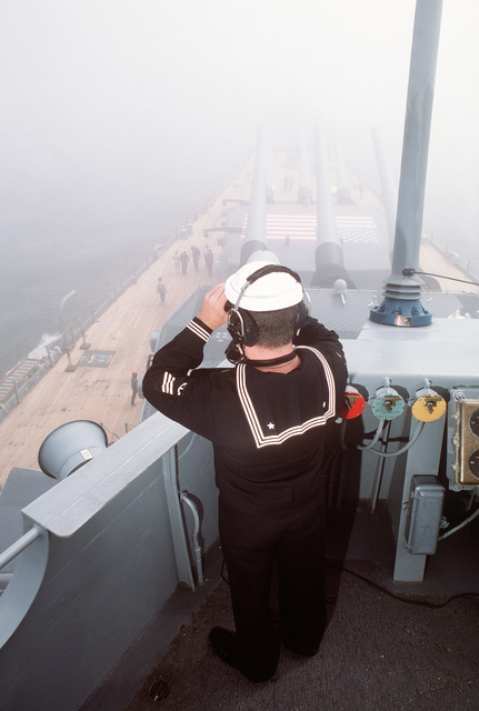 A seaman aboard the battleship USS IOWA (BB 61) uses binoculars to check visibility during a dependen'ts cruise between Naval Weapons Station, Yorktown, Virginia, and Naval Base, Norfolk, Virginia. He is using a sound-powered telephone to relay information to the pilot house