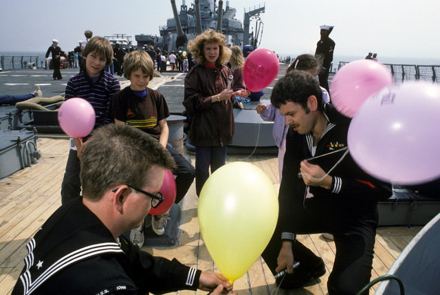 Crewmen aboard the battleship USS IOWA (BB 61) fill balloons for dependent children during a cruise from Naval Weapons Station, Yorktown, Virginia, to Naval Base, Norfolk, Virginia