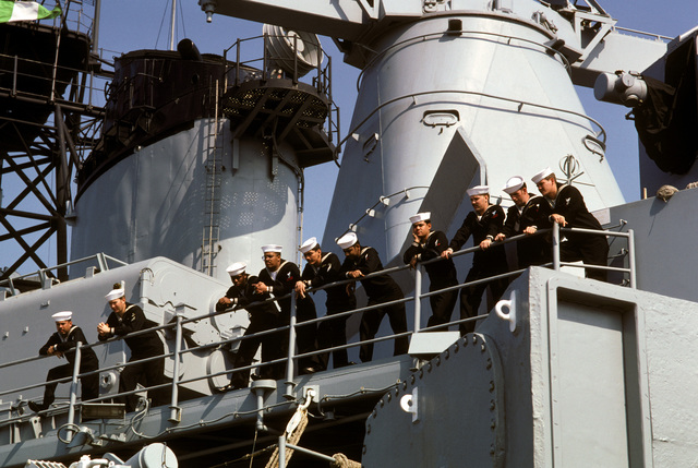 Crewmen stand along a rail aboard the battleship USS IOWA (BB 61). The IOWA is on a family cruise between Naval Weapons Station, Yorktown, Virginia, and Naval Base, Norfolk, Virginia