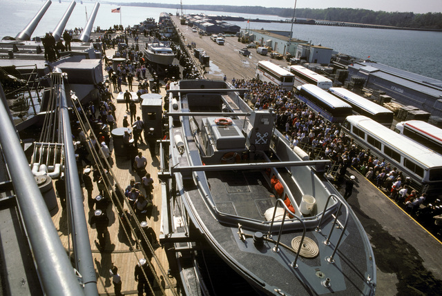 Dependents stand on the pier waiting to board the battleship USS IOWA (BB 61) for a six-hour cruise to Naval Base, Norfolk, Virginia