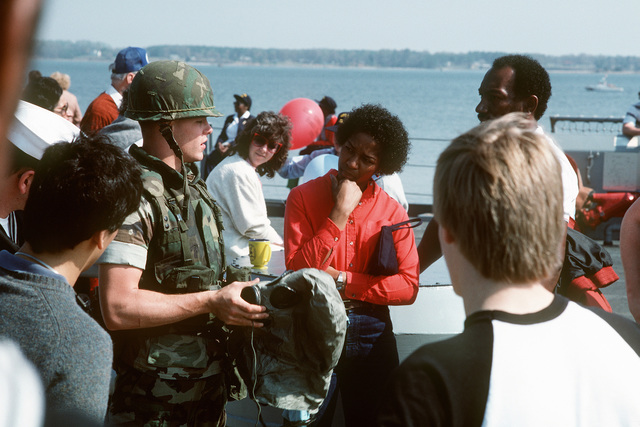 Dependents talk to a Marine aboard the battleship USS IOWA (BB 61) during a cruise from Naval Weapons Station, Yorktown, Virginia, to Naval Base, Norfolk, Virginia. He is explaining the function of nuclear-biological-chemical (NBC) protective gear