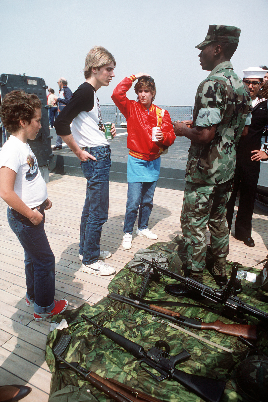 Dependents talk to a Marine aboard the battleship USS IOWA (BB 61) during a cruise from Naval Weapons Station, Yorktown, Virginia, to Naval Base, Norfolk, Virginia. Weapons visible on the deck are M14 and M16A1 rifles, foreground, a 12-gauge shotgun and an M60 machine gun