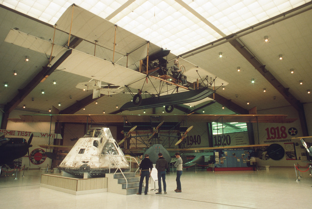 A replica of the Curtiss pusher seaplane designated A-1 is suspended from the ceiling of the US Naval Aviation Museum. The A-1 was the first aircraft purchased by the Navy. Below is the Skylab command module that was manned by an all-Navy crew during a 1973 spaceflight. All Hands - April 1985