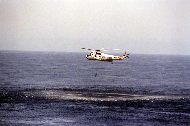 A Helicopter Anti-submarine Squadron 2 (HS-2) SH-3H Sea King helicopter deploys an AQS-13 dipping sonar during a routine anti-submarine warfare patrol