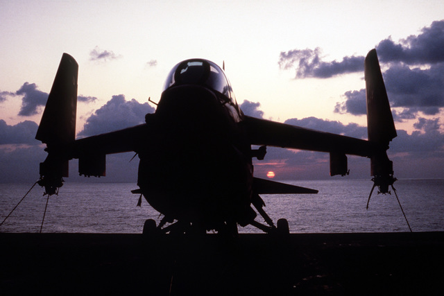 A front view of an A-7 Corsair II aircraft silhouetted against the setting sun aboard the nuclear-powered aircraft carrier USS CARL VINSON (CVN 70)