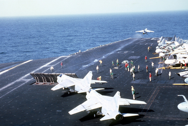 An A-7 Corsair II aircraft takes off from the deck of the nuclear-powered aircraft carrier USS CARL VINSON (CVN 70). Two other A-7s wait their turn. Various other aircraft are parked on the right