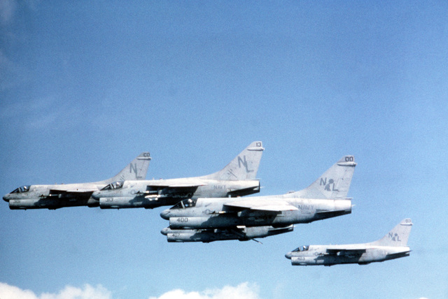 An air-to-air left side view of five A-7 Corsair II aircraft. The aircraft are armed with AIM-9 Sidewinder missiles