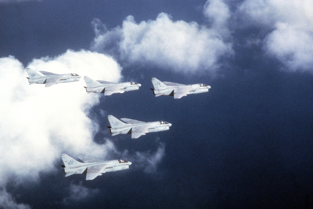 An air-to-air right side view of five A-7 Corsair II aircraft flying in formation