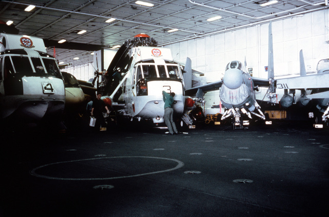 An interior view of the hangar deck aboard the nuclear-powered aircraft carrier USS CARL VINSON (CVN 70). Two SH-3 Sea King helicopters are parked on the left and an A-7 Corsair II aircraft is on the right