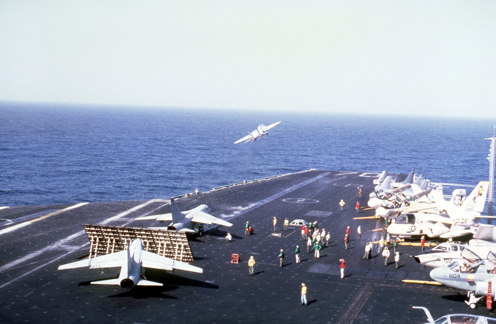 Elevated view of the flight deck aboard the nuclear-powered aircraft carrier USS CARL VINSON (CVN 70). An F-14 Tomcat has just taken off and an A-7 Corsair II aircraft is waiting for launch. Various aircraft are parked on the right