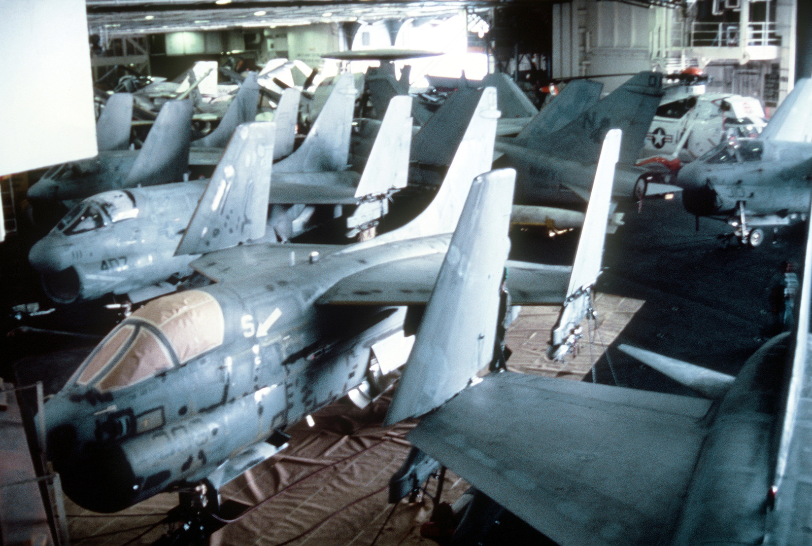 Interior view of the hangar deck, with parked A-7 Corsair II aircraft, aboard the nuclear-powered aircraft carrier USS CARL VINSON (CVN 70)