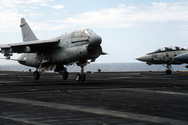 Right front view of an A-7 Corsair II aircraft landing aboard the nuclear-powered aircraft carrier USS CARL VINSON (CVN 70). An F-14 Tomcat aircraft is on the right