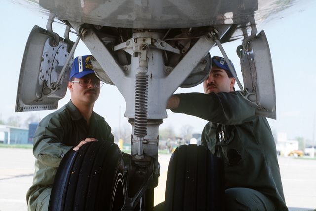 AIRMAN (AMN) John Samson, left, and Sergeant (SGT) Mike Manley, right, of the 375th Consolidated Aircraft Maintenance shop inspect the landing gear on a C-9 Nightingale aircraft