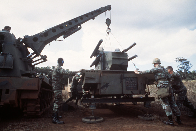 Personnel of the 1ST Battalion, 62nd Air Defense Artillery, remove an M-54 Chaparral missile launcher from a tracked vehicle in preparation for air transport during Exercise COPE CANINE '85