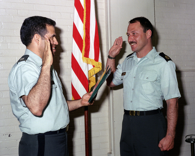 Sergeant First Class (SFC) Raymond R. Sellars is sworn in for a six-year re-enlistment by Captain (CPT) Louis D. Cruz, a unit commander at Rock Island Arsenal