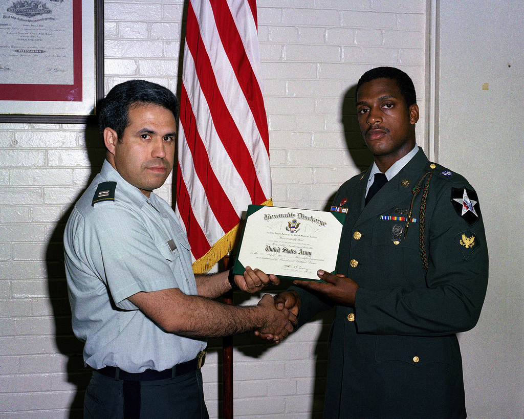 SPECIALIST 4 (SPC) Rick Mitchell receives his discharge certification from Captain (CPT) Louis D. Cruz, a unit commander at Rock Island Arsenal, before being sworn in for another three-year enlistment