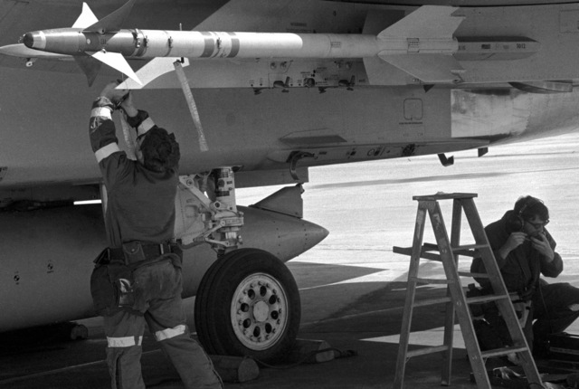 A ground crewman inspects an AIM-9L Sidewinder missile aboard an F-15 Eagle aircraft during a 1ST Tactical Fighter Wing operational readiness inspection