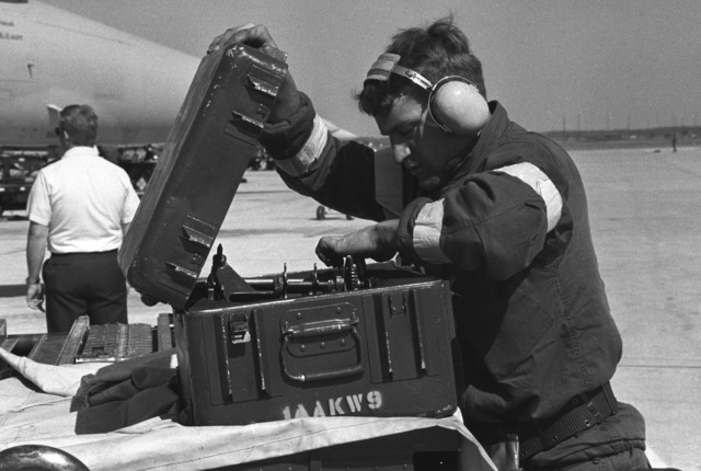 A ground crewman unpacks a piece of equipment while loading ammunition aboard an F-15 Eagle aircraft during a 1ST Tactical Fighter Wing operational readiness inspection