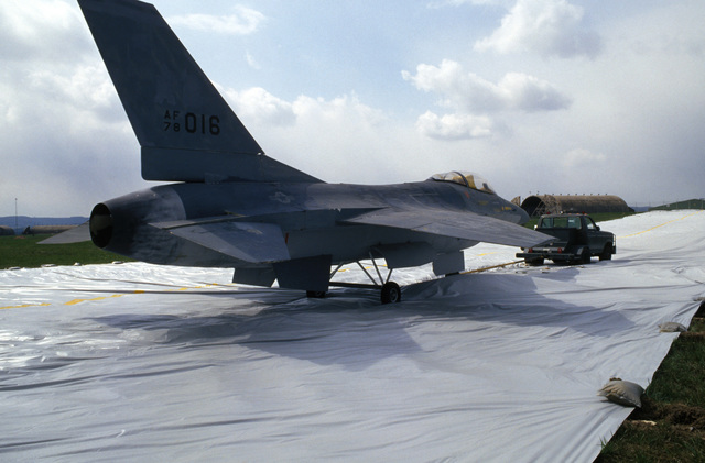 A mockup of an F-16 Fighting Falcon aircraft is towed onto a fake taxiway to confuse attacking opposing force aircraft during Exercise SALTY DEMO'85.  SALTY DEMO'85 is an air base survivability exercise evaluating passive and active defenses, aircraft operation and generation, and base recovery systems