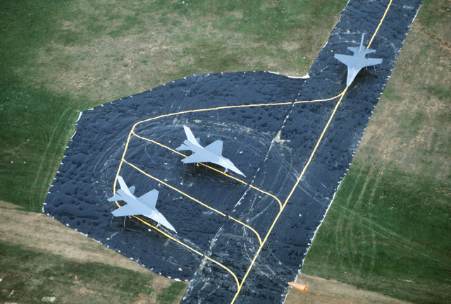 An aerial view of F-16 Fighting Falcon aircraft mockups parked on a fake flight line during Exercise SALTY DEMO'85.  SALTY DEMO'85 is an air base survivability exercise evaluating passive and active defenses, aircraft operation and generation, and base recovery systems