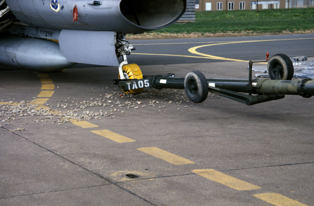 An F-16 Fighting Falcon aircraft is backed over rocks to demontrate the protective resilience of the flow tracks fitted to its tires during Exercise SALTY DEMO'85.  SALTY DEMO'85 is an air base survivability exercise evaluating passive and active defenses, aircraft operation and generation, and base recovery systems