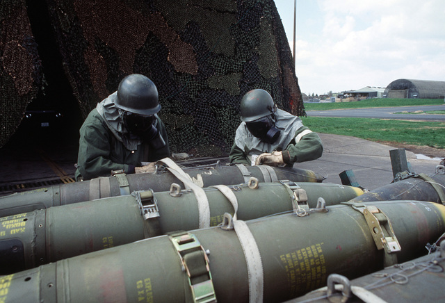 Ground crew personnel, dressed in chemical warfare protection suits, secure Mark 82 500-pound bombs onto a weapons carrier during Exercise SALTY DEMO'85.  SALTY DEMO'85 is an air base survivability exercise evaluating passive and active defenses, aircraft operation and generation, and base recovery systems