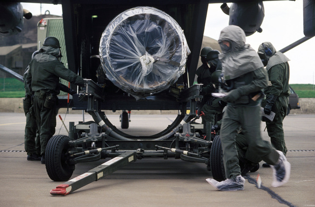 Ground crew personnel, dressed in chemical warfare protection suits, unload an aircraft engine from the rear hatch of a C-23A Sherpa aircraft during Exercise SALTY DEMO'85.  SALTY DEMO'85 is an air base survivability exercise evaluating passive and active defenses, aircraft operation and generation, and base recovery systems