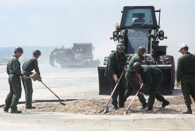 Members of the 2853rd Civil Engineering Squadron rapid runway repair team finish repairing a bomb crater in the runway by spreading rocks throughout the hole during Exercise SALTY DEMO'85.  SALTY DEMO'85 is an air base survivability exercise evaluating passive and active defenses, aircraft operation and generation, and base recovery systems