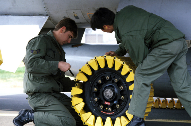 Members of the 50th Equipment Maintenance Squadron secure a flow track to an aircraft tire during Exercise SALTY DEMO'85.  The flow track protects the tire when an aircraft is towed over rocks, mud or snow. SALTY DEMO'85 is an air base survivability exercise evaluating passive and active defenses, aircraft operation and generation, and base recovery systems