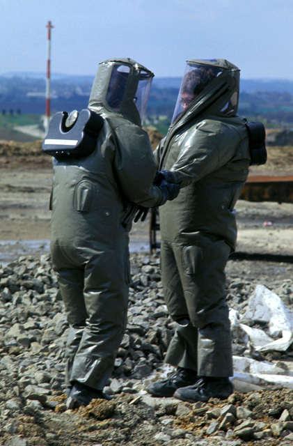 Members of the 52nd Civil Engineering Squadron rapid runway repair crew, dressed in impermeable chemical defense protective ensemble systems (IMPS), fill a manufactured bomb crater during Exercise SALTY DEMO'85.  SALTY DEMO'85 is an air base survivability exercise evaluating passive and active defenses, aircraft operation and generation, and base recovery systems