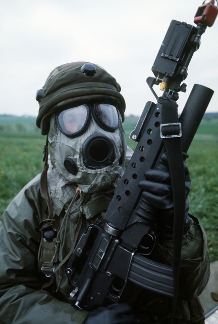 PFC. Albert Norling, Battery A, 656th Air Defense Artillery, stands guard dressed in chemical warfare gear during Exercise Salty Demo '85. Salty Demo '85 is an air base survivability exercise evaluating passive and active defenses, aircraft operation and generation, and base recovery systems. Norling's M-16A1 rifle is equipped with an M-203 40mm grenade launcher and a multiple integrated laser engagement system (MILES) transmitter