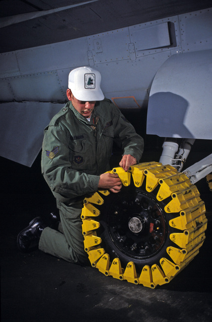 Senior AIRMAN (SRA) Michael Rathman, 50th Equipment Maintenance Squadron, pins a flow track together on the tire of an F-16 Fighting Falcon aircraft during Exercise SALTY DEMO'85.  SALTY DEMO'85 is an air base survivability exercise evaluating passive and active defenses, aircraft operation and generation, and base recovery systems