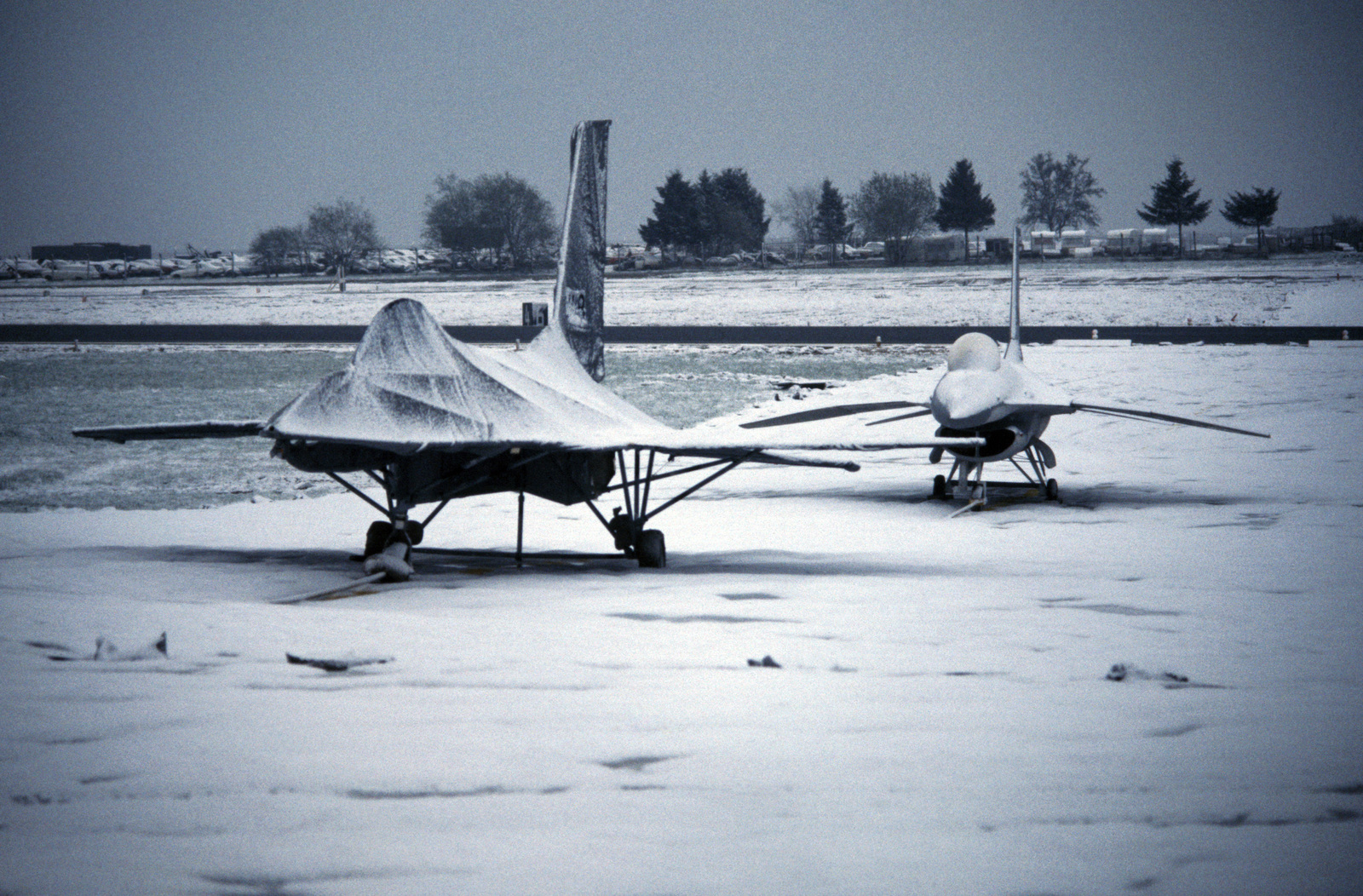Snow-covered F-16 Fighting Falcon aircraft mockups rest on a fake taxiway during Exercise SALTY DEMO'85.  SALTY DEMO'85 is an air base survivability exercise evaluating passive and active defenses, aircraft operation and generation, and base recovery systems