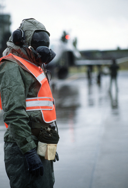 Technical Sergeant (TSGT) Paul Paulus, dressed in a chemical warfare protection suit, guides aircraft into parking spots on the flight line during Exercise SALTY DEMO'85.  SALTY DEMO'85 is an air base survivability exercise evaluating passive and active defenses, aircraft operation and generation, and base recovery systems