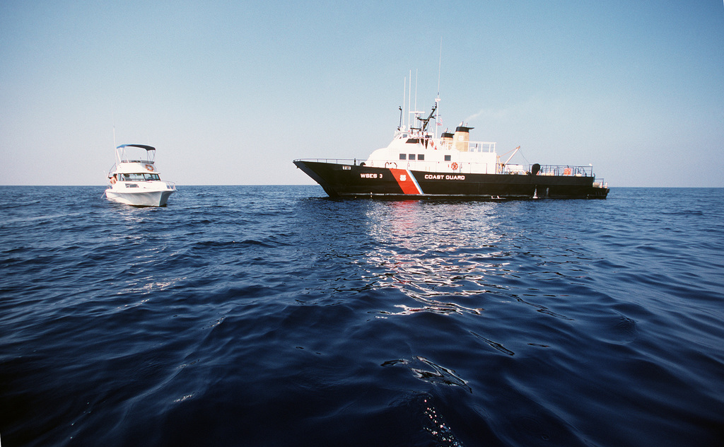 The surface effect ship (SES) USCGC SHEARWATER (WSES 3) approaches a private craft on the open ocean. The SHEARWATER is primarily used in the drug enforcement role - PICRYL Public Domain Image