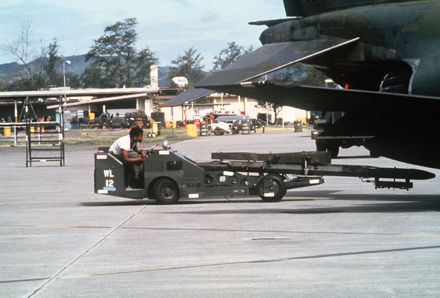 A ground crewman uses a weapons loader to position a bomb rack underneath the wing of an F-4 Phantom II aircraft