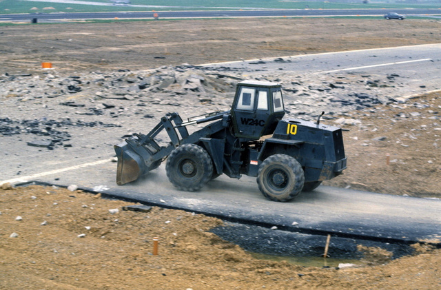 A Case W24 four-wheel drive loader moves onto the runway to begin reconstruction after a simulated attack during Exercise SALTY DEMO'85.  SALTY DEMO'85 is an air base survivability exercise evaluating passive and active defenses, aircraft operation and generation, and base recovery systems