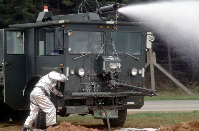 A fire truck from the Spangdahlem fire department sprays foam on a fuel pit fire started by an evaluation team during Exercise SALTY DEMO '85. SALTY DEMO '85 is an air base survivability exercise evaluating passive and active defenses, aircraft operations and generation, and base recovery systems