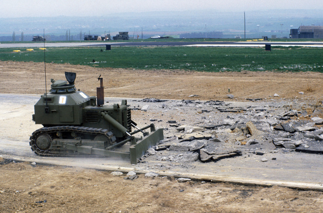 An armored bulldozer operated by the 7007th Explosive Ordnance Disposal Flight clears debris and unexploded ordnance from the runway after a simulated air attack during Exercise SALTY DEMO'85.  SALTY DEMO'85 is an air base survivability exercise evaluating passive and active defenses, aircraft operation and generation, and base recovery systems