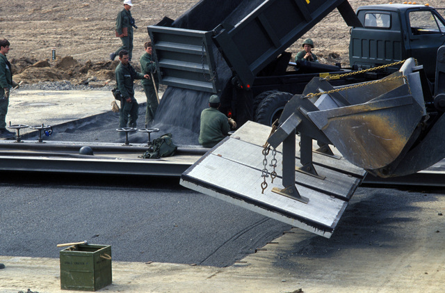 Members of the 819th Civil Engineering Squadron rapid runway repair team dump pea gravel into a bomb crater while a tractor prepares to cap the hole with prefabricated cement slabs during Exercise SALTY DEMO'85.  SALTY DEMO'85 is an air base survivability exercise evaluating passive and active defenses, aircraft operation and generation, and base recovery systems