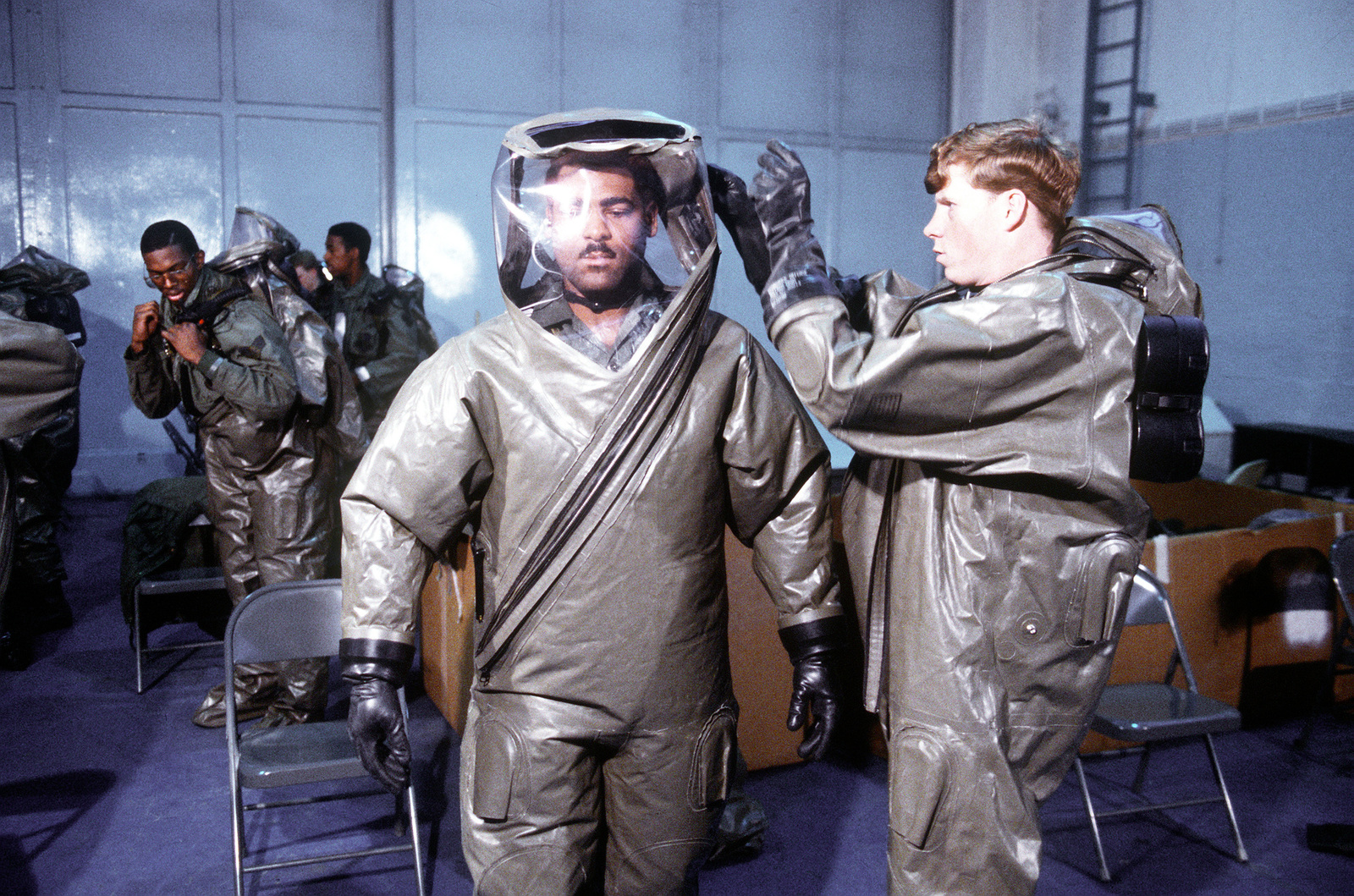 Sergeant Lysle Glass, 52nd Aircraft Generation Squadron, helps Staff Sgt. Charles Cooks, also from the 52nd AGS, get into an impermeable chemical defense protective ensemble system (IMPS) during exercise Salty Demo '85. Salty Demo '85 is an air base survivability exercise evaluating passive and active defenses, aircraft operation and generation, and base recovery systems