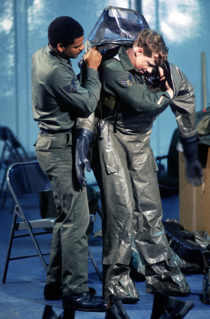 Staff Sergeant Charles Cooks, 52nd Aircraft Generation Squadron, helps Sergeant Lysle Glass, also from the 52nd AGS, get into an impermeable chemical defense protective ensemble system (IMPS) during Exercise SALTY DEMO '85. SALTY DEMO '85 is an air base survivability exercise evaluating passive and active defenses, aircraft operation and generation, and base recovery systems