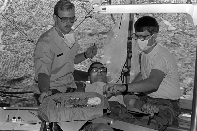 A Navy dentist and his assistant from the Twentynine Palms branch dental clinic treat a Marine in a tent in the field